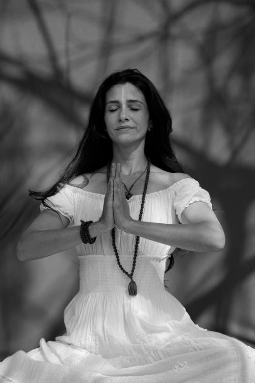 Black and white of tranquil female with closed eyes and folded hands meditating while sitting in forest on blurred background