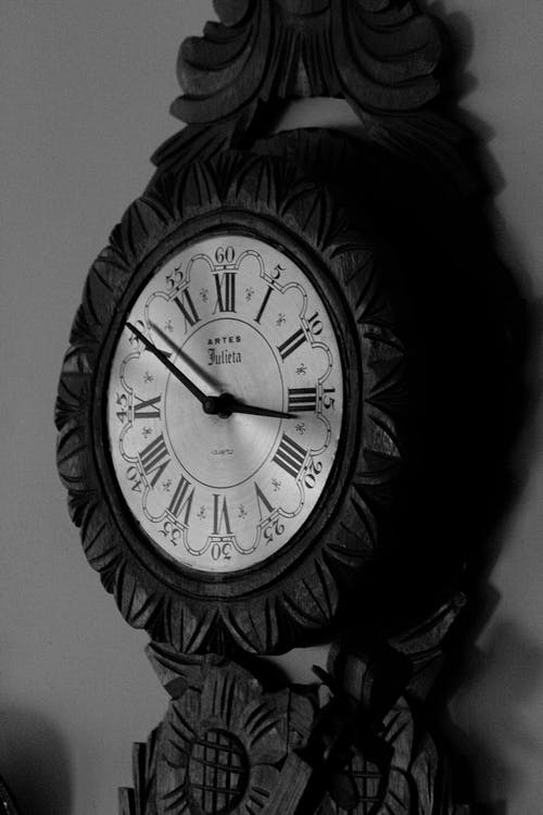 Black and white of round old fashioned clock with dial and curved ornamental details with retro design placed on blurred background