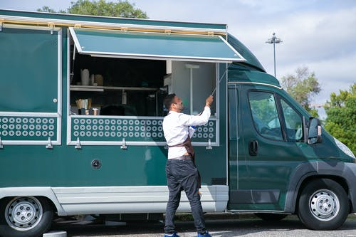 Side view young waiter in apron standing outside food truck and opening counter door in green lush park