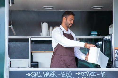 Waiter standing at food truck counter with paper towel