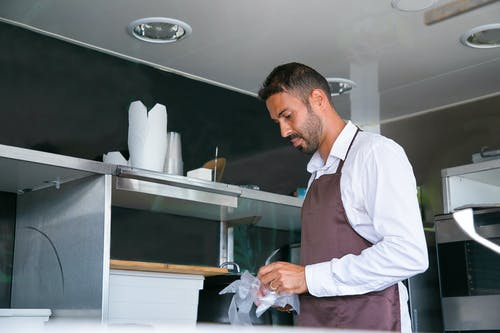 Side view of ethnic man putting on cellophane gloves while working in kitchen of cafe