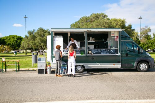 Couple standing near food truck and choosing food