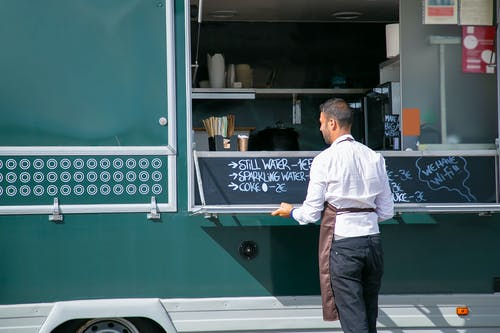 Back view of male seller wearing apron preparing food truck with menu written on board