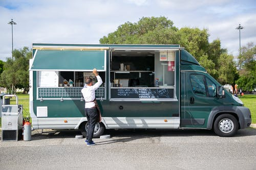 Back view full body of anonymous male worker opening windows of car with street food parked in park