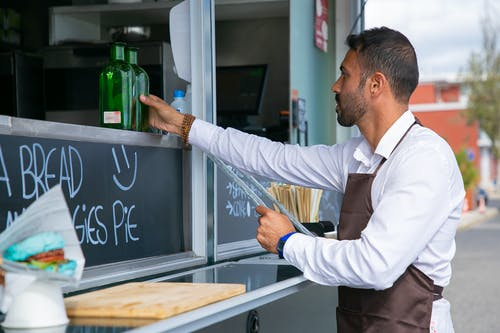 Focused ethnic male worker placing glass bottle at counter