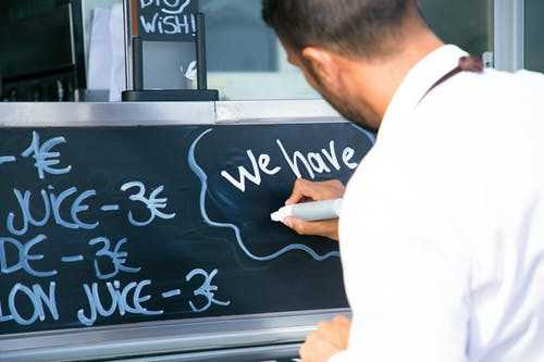Back view of crop anonymous male worker writing information on marker board for clients of food truck