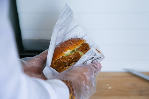 Cook wrapping sandwich in paper package