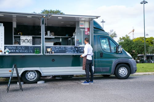 Back view full body of anonymous man in apron standing near food trailer with counter and menu on board