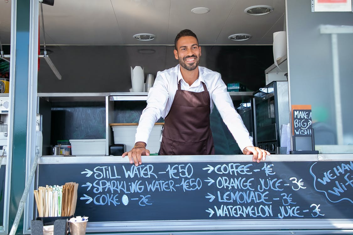 Low angle of ethnic seller wearing uniform standing at counter in food trailer and smiling happily