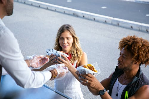 High angle of positive multiracial couple getting delicious burgers from salesman working in food truck