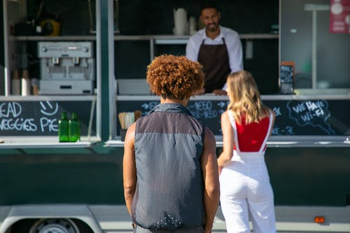 Back view of diverse clients standing near street food truck and choosing lunch
