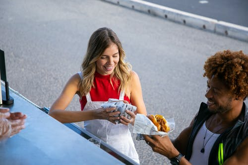 From above of positive multiethnic couple eating tasty burgers wrapped in paper at food truck