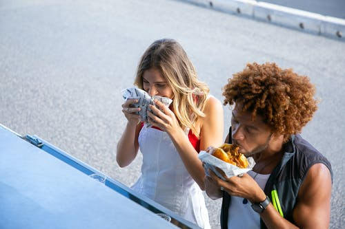High angle of diverse hungry couple having lunch with burgers together at food truck