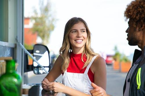 Positive female talking to black boyfriend near food truck