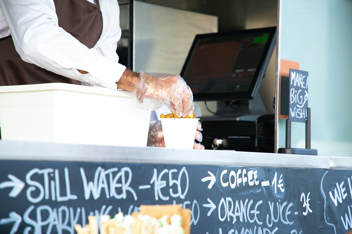 Low angle of crop anonymous male seller with cup of fried food at counter with cashier