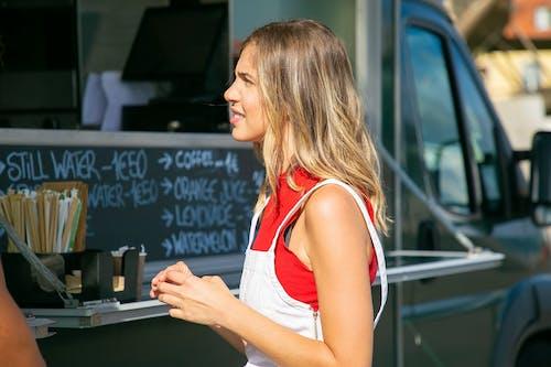 Young woman choosing food at street food counter