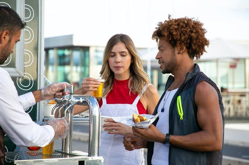 Seller pouring beer to diverse couple