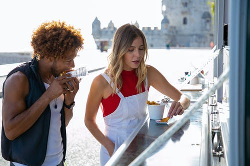 Woman eating fried potato with sauce standing near black boyfriend biting tasty burger at food truck