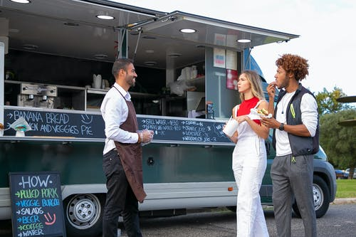 Side view of happy young ethnic waiter in uniform standing near food van and smiling while greeting diverse customers eating delicious takeaway burger and french fries