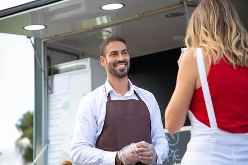 Happy young ethnic waiter looking at anonymous client having lunch near truck cafe