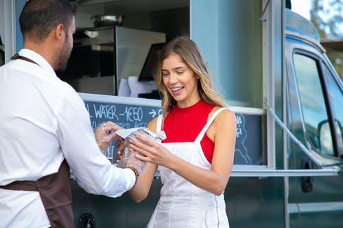 Waiter serving delicious hamburger for cheerful female customer in road cafe