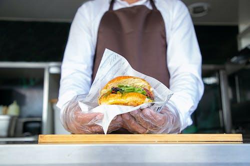 Cocinero De Pie En El Camión De Comida Y Dando Hamburguesa