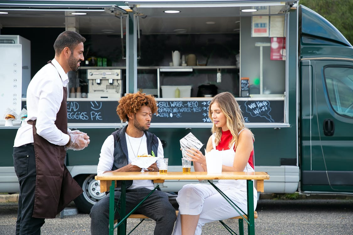 Cheerful owner of food truck standing near table with diverse couple eating burgers and resting on street in daytime