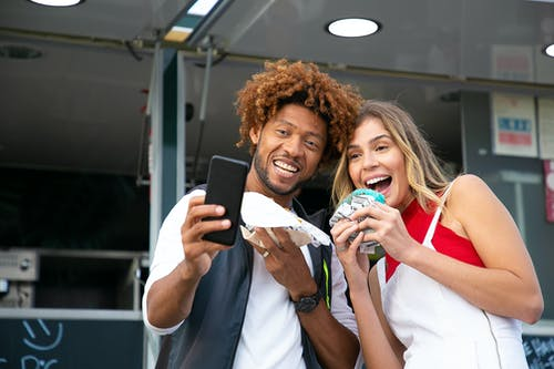 Happy friends taking selfie with tasty burgers