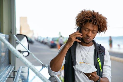 Black man talking on smartphone while eating burger on street