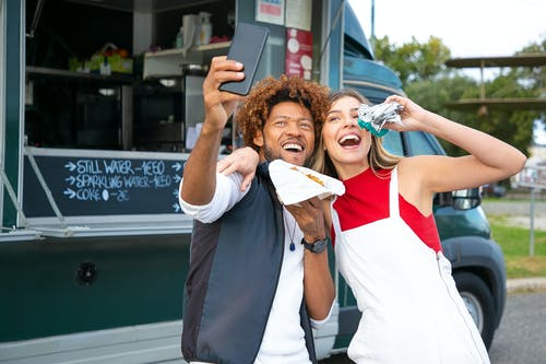 Joyful multiracial friends embracing and taking selfie on cellphone while eating tasty burgers near food truck in lush park