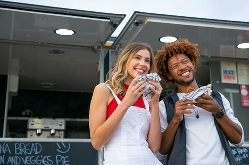 Delighted young multiracial friends wearing casual outfits enjoying delicious burgers and looking away with smiles while standing near street food truck