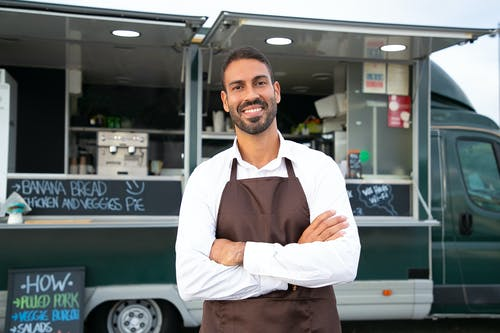 Smiling young ethnic male waiter in apron standing with arms folded near modern food truck and looking at camera contentedly
