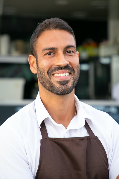 Cheerful ethnic waiter in apron standing against street cafe