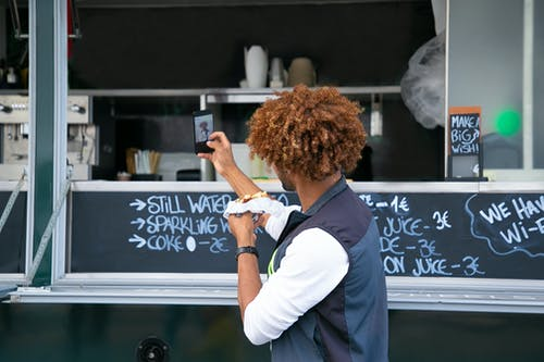 Side view unrecognizable African American male in casual clothes eating yummy sandwich near food truck and taking selfie on mobile phone