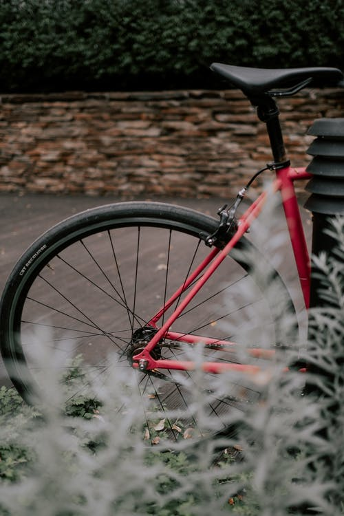 Red Bicycle Wheel Leaning on Brown Brick Wall