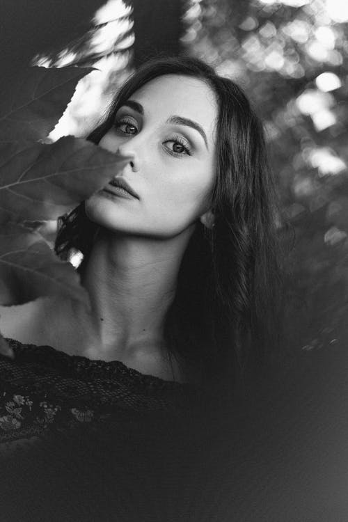 Black and white of young female with light makeup in elegant lace clothes standing in forest and holding maple leaf while looking at camera