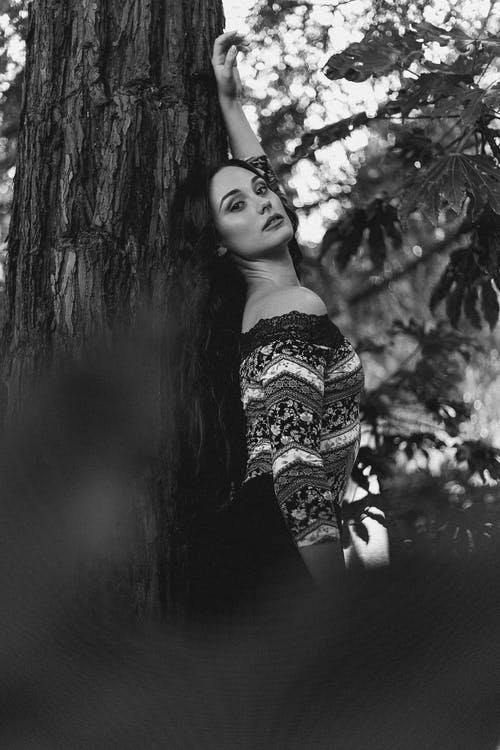 Stylish woman leaning on tree in forest