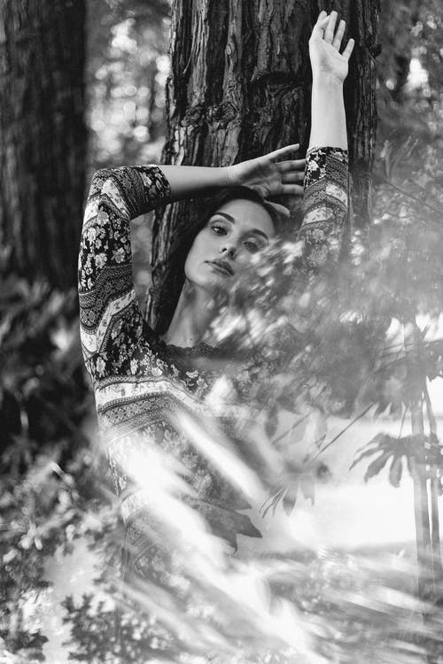 Through glass of charming female leaning on tree trunk with raised arms and looking at camera