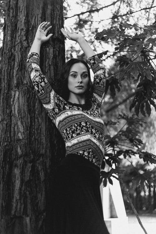 Woman leaning on tree trunk in forest