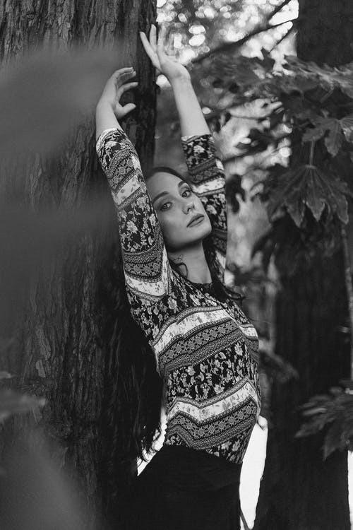 Black and white of young female in casual clothes leaning on tree in forest with raised hands and looking at camera