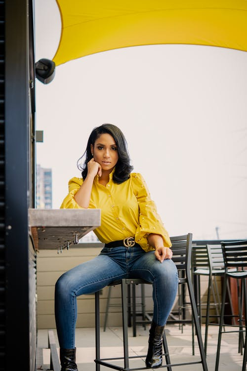 Woman in Yellow Long Sleeve Shirt and Blue Denim Jeans Sitting on Brown Wooden Bench