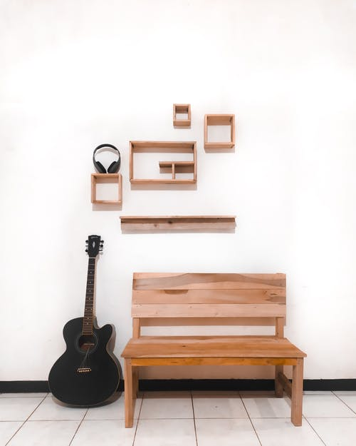 Black Acoustic Guitar on Brown Wooden Bench