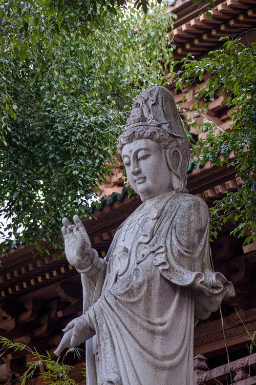 Traditional stone sculpture of Buddha placed near building in oriental style and tree with lush foliage on street in city