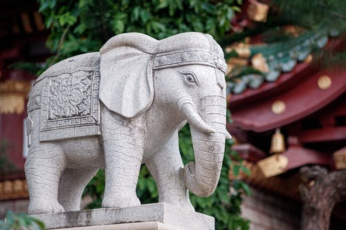 Traditional stone sculpture of elephant placed near oriental styled local house and plant with green vegetation on street in city