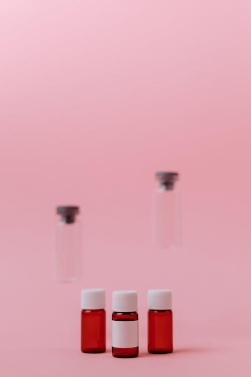 粉紅色的表面上的三個小玻璃瓶