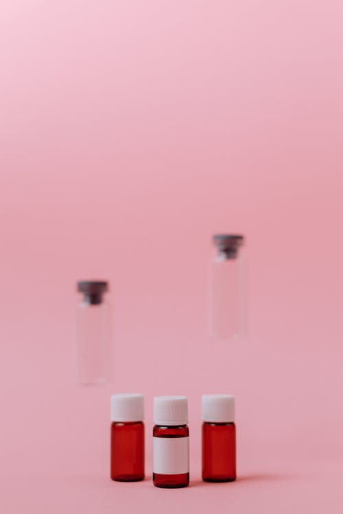 Tiga Botol Kaca Kecil Di Permukaan Merah Muda