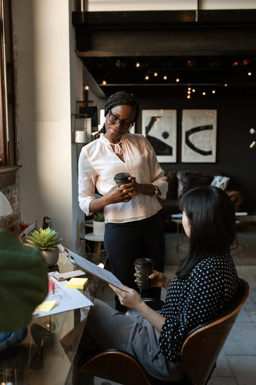Multiracial female coworkers chatting in stylish office during coffee break