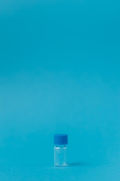 Tiny Bottle on Blue Surface
