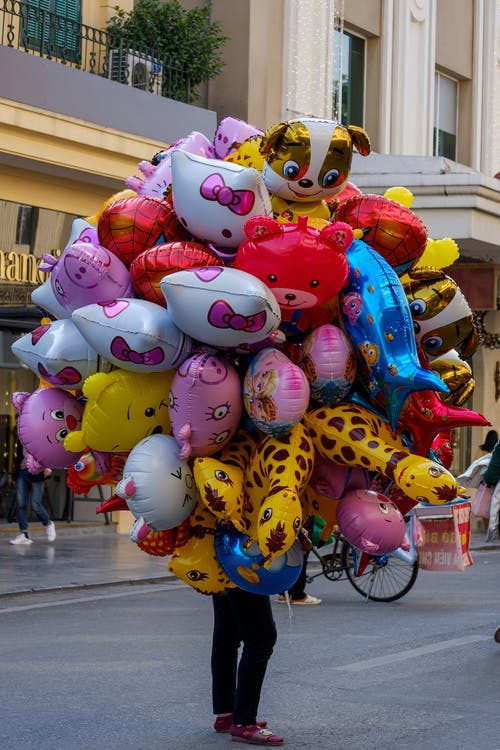Unrecognizable seller with colorful helium balloons in shape of animals standing on sidewalk on street in city during festive event