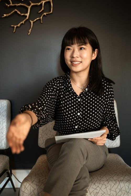 Woman in Black and White Polka Dot Long Sleeve Shirt Sitting on Brown Sofa